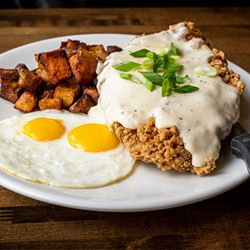 Spokane Brunch atBruncheonette Chicken Fried Steak topped with Country Gravy, Country Potato Medley, and 2 Eggs your way